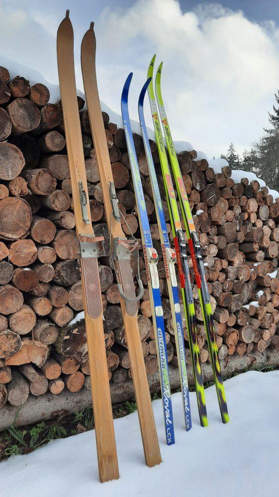 Ein Paar alte Holzski, ein Paar Germina Ski und ein Paar Fischer Ski stehen nebeneinander